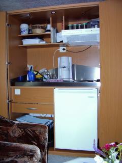 Blick in die Schrankküche (2Kochplatten, Abwäsche, Kühlschrank)