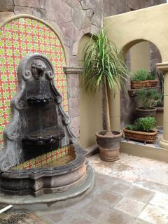Patio fountain with pots of fresh herbs for the cook