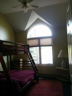 This bedroom with bunkbeds and trundle bed