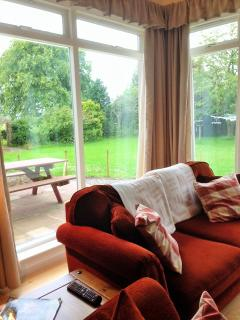 Sitting room leading to enclosed patio area overlooking woodland garden