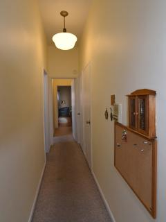A long hallway separates the bedrooms from the kitchen and living/dining room.