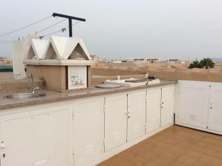 Roof terrace kitchen and storage cupboards with sun bed area plus dining area.