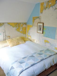 The guest bedroom is decorated with old nautical maps. (Full-sized bed)