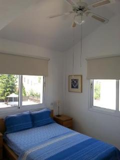 Master bedroom with double bed, cuboard, airconditioning unit and ceiling fan