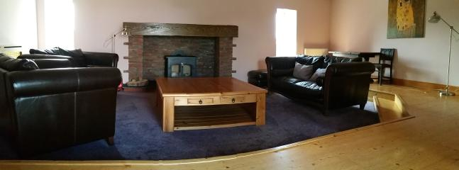 large formal lounge , with over sized furniture to sink into infront of the huge wood burning stove