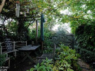 Paved sitting area in garden under pergola