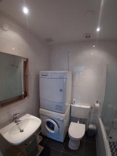 Bathroom with washing basin, toilet, bath/shower, washing machine and dryer.
