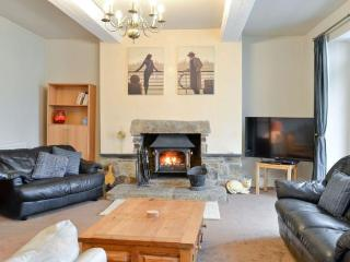 The leather sofas are arranged around the large log burner in the welcoming sitting room.