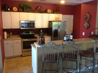 New stainless appliances in kitchen with room for four at bar.