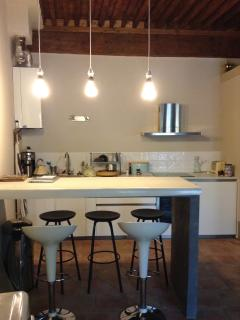 Kitchen with polished concrete bar for dining and designer pendant lighting