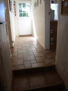 Tiled hallway with Breakfast kitchen to right and bathroom to left