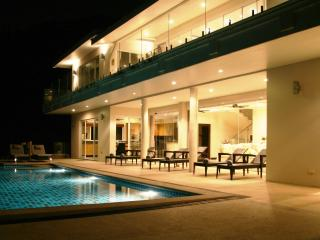 Night view of pool and front of house