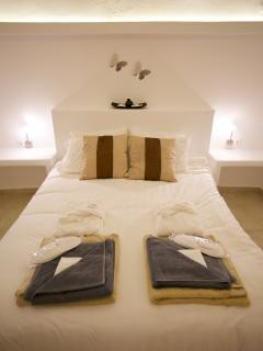 Bedroom set up for the next guests ,set up with bathrobe, slippers, bath towel, face towel and