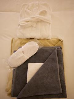 Guest set up with bathrobe, slippers, bath towel, face towel and Jacuzzi towel.