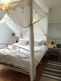 spacious bedroom with King sized bed, bedside lamps, tables, shelving and lovely wooden floor