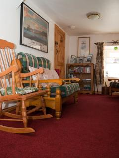 View of living room with rocking chair and cosy sofa.