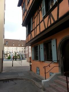 L'entrée du gîte, à droite, avec vue sur la place du 2 Février et la médiathèque au fond. .