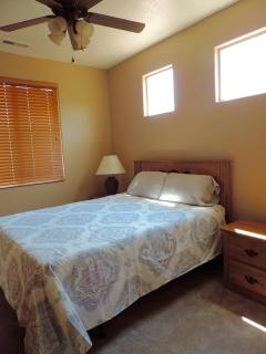 guest bedroom has queen bed and dresser, nightstand