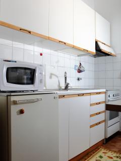 La cucina completa di stufa con forno, frigorifero e forno a microonde