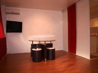 Téléviseur HD 80 cm, table ronde en verre avec ses quatre poufs.