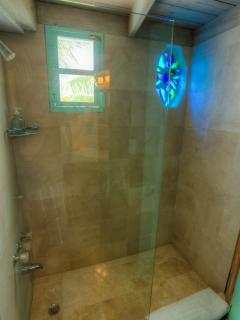 New marble shower with beach glass stained glass window