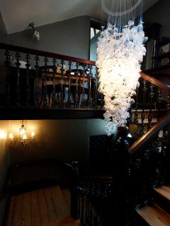 The stairwell leading up to the bedroom, featuring a chandelier made with 300 crystal wine glasses.