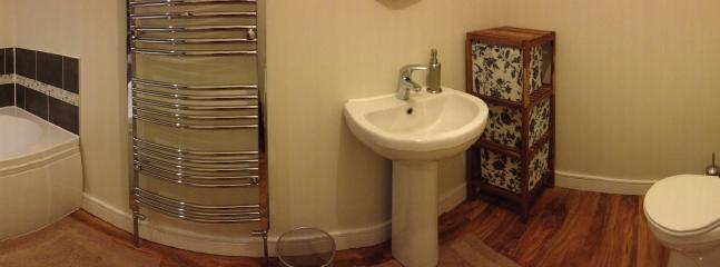 Bathroom has a full size P shaped  showerbath with shower head, toilet sink and storage.