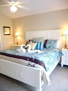 Master suite with sliding doors to patio/pool and en suite bathroom, TV.