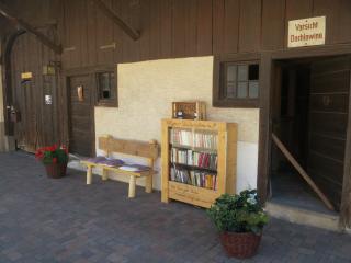 Sitzmöglichkeit vor dem Haus mit offenem Bücherschrank