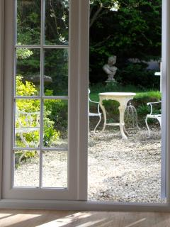 French windows leading to pretty garden area, with seating and barbecue.