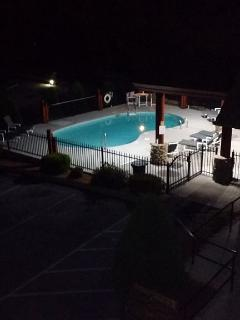 Outdoor pool and hot tub after dark