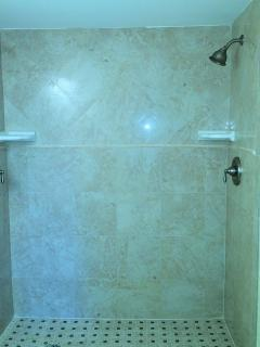 Completely remodeled bath with double shower, Italian porcelain tile, granite topped vanity