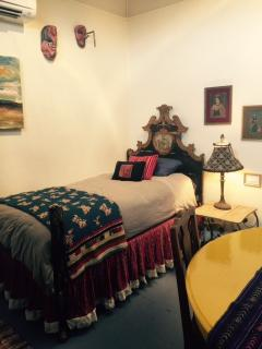 2nd bedroom area has an antique portuguese twin bed, next to the 'Monet yellow' dining table