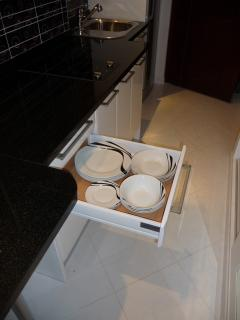 Second drawer opened with various plates of different sizes for 4 persons