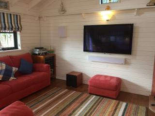Lounge area with double sofers, 55inch TV,  7.1 surround sound system, wood burner and reading lamp.