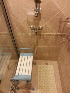 Seat in shower room with plastic mats on floor and level of shower adapted for wheelchair users