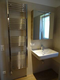 The family bathroom has a shower, wc, sink and heated towel rail