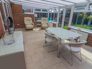 Garden Room with dining table and chairs, reclinging armchairs, double and single doors to garden