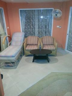 Seating place in front of second guestroom by night, with 2 dimmable ceiling lamps and fan