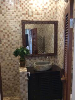 Exhotic bathroom with stone hand basin and large mirror