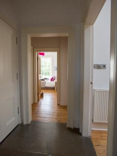 the hall through to bed 1 and the kitchen and living room on the right