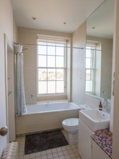 the bathroom with bath and shower over