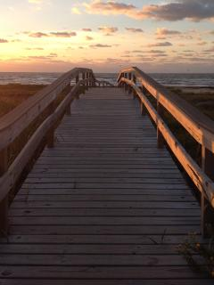 Sea Isle's boardwalk over the dunes to the beach at sunrise.