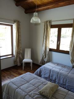 the second bedroom has glass window and window overlooking the forest and the surrounding countrysid