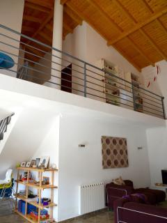 The living area has a double height ceiling with a mini library and reading area