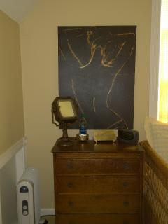 Art above the lighted magnification mirror on top of vintage dresser with brass pulls.