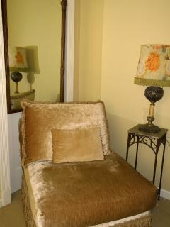 Velvet lounging chair in front of vintage mirror and converted oil lamp.