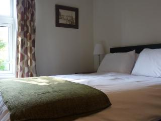 The comfortable double bed has a lovely view of the garden.