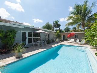 The Pool and 2 bedroom apartment shown behind red umbrella.