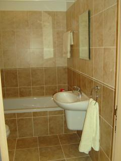 Fully tiled bathroom with bath shower and extractor fan  .Picture  doesn't display features